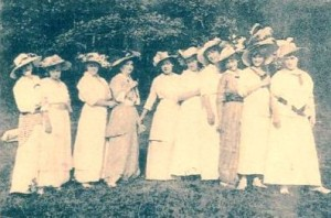 A group of ladies standing on a green lawn with old-fashioned floor length dresses and hats
